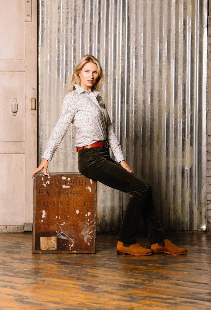 Model sitting on box wearing white shirt, green corduroy trousers and tan chelsea boots