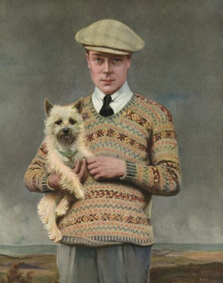 The Price of Wales holding dog and wearing geometric patterned wool jumper.