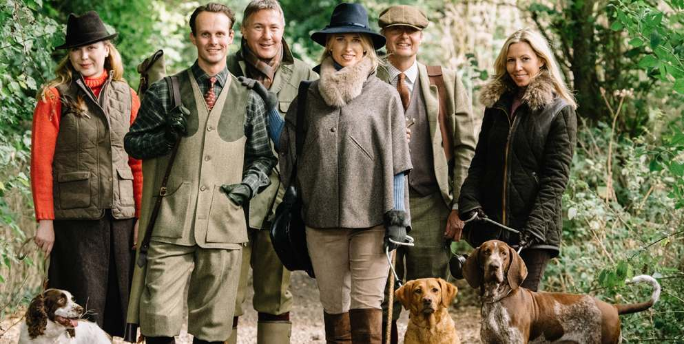 Cordings models pose with shooting dogs in tweed field and shooting clothes
