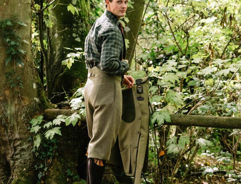 Man stood in woodland looking over his shoulder towards camera wearing a green checked shirt and tweed fish tail back plus fours.