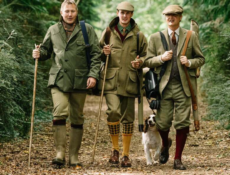 Three men in shooting outfits with shooting equipment walking through a forest with a dog.