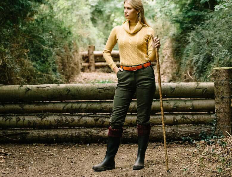 Woman standing in a wooddland by logs wearing boots, green breeks, and a yellow knitted jumper.