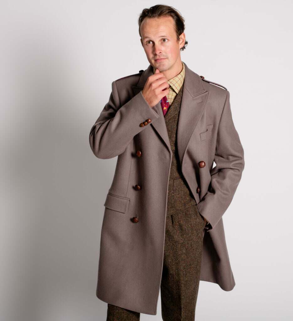 A model wears a Cordings' British Warm Coat over a classic Donegal Tweed Suit