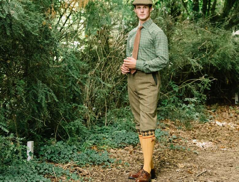 Man wearing tweed breeks, and a green shirt with brown tie, standing in the field.
