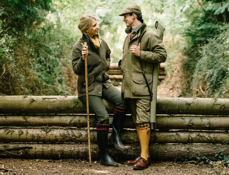 A man and a woman leaning on stacked logs in a forest, wearing tweed shooting outfits.